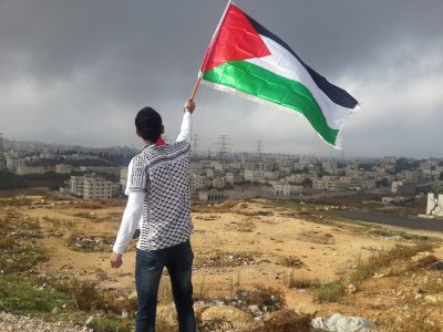 Man waving Palestine flag, showing the importance of international solidarity.